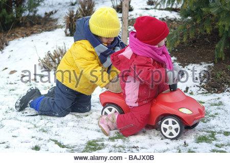 Coppia di bambini che giocano la neve a lunghezza piena ragazza ragazzo giocattolo dei giocattoli giocare giocare Foto Stock