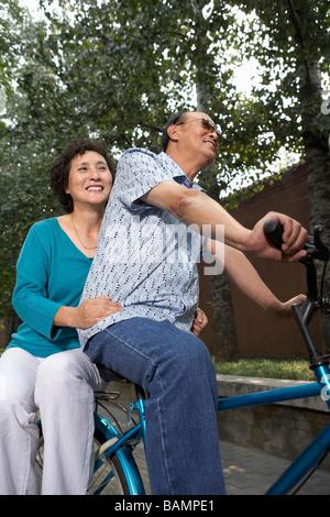 Ritratto di un uomo e di una donna su una bicicletta Foto Stock