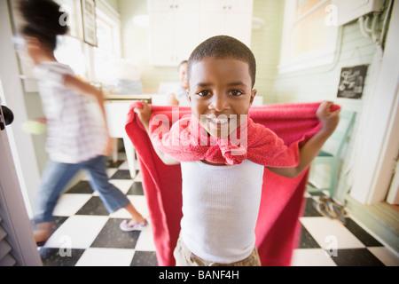 Razza mista boy usando un asciugamano per riprodurre il supereroe