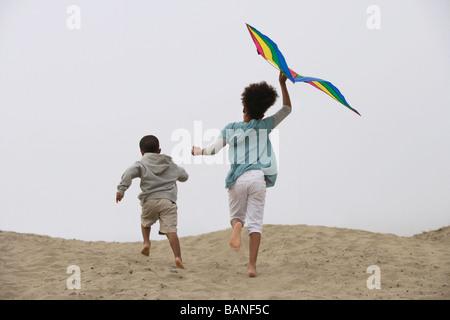 Razza mista i bambini in esecuzione sulla spiaggia con kite Foto Stock