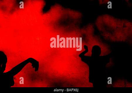 I bambini che gettano ombre su una ruvida parete rossa Foto Stock