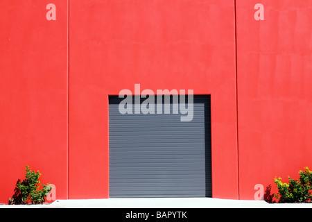 Rullo grigio porta di garage in rosso e parete di mattoni Foto Stock