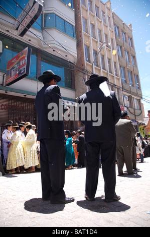 Due uomini in abiti guarda la celebrazione sulla strada a La Paz in Bolivia Foto Stock