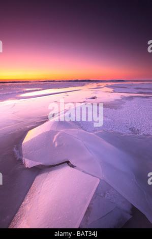 Un lago ghiacciato brilla nel crepuscolo del mattino Foto Stock