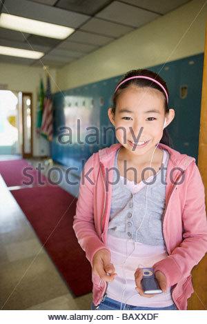 Ragazza ascoltando mp3 player nel corridoio della scuola Foto Stock