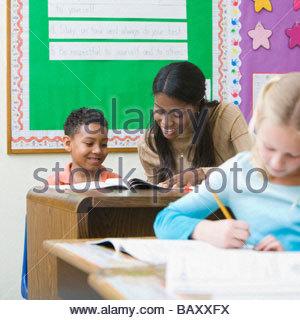 Insegnante aiutando il ragazzo con il lavoro della scuola Foto Stock