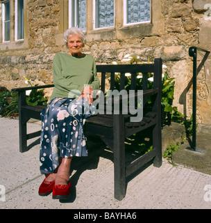 Anziani donna seduta al di fuori di casa sua. Foto Stock