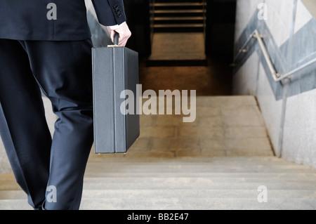 Imprenditore portando una valigetta andando giù per le scale per una stazione della metropolitana vista posteriore Foto Stock