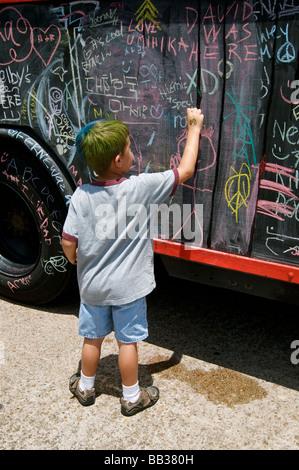 Ragazzo giovane scrive in gesso su arte auto in Houston parade Foto Stock