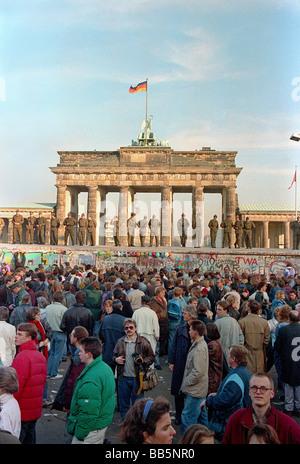 La folla nella parte anteriore del muro di Berlino e Porta di Brandeburgo nel 1989, Berlino, Germania Foto Stock