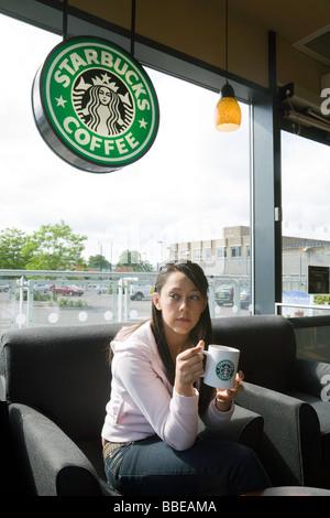 Un adolescente ragazza teen di bere il caffè di Starbucks, Cambridge, Regno Unito Foto Stock