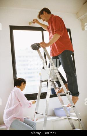 Giovane pittura parete assieme, uomo in piedi sulla scaletta Foto Stock