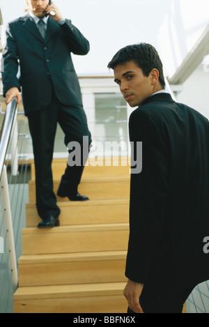 Imprenditore salire le scale, guardando sopra la spalla in telecamera Foto Stock