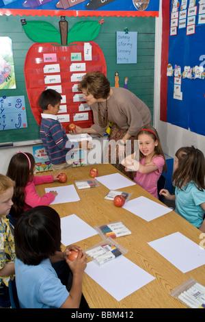 Bambini elementari multi etnico razziale diversità multiculturale ragazzo ispanico che passano fuori mele foto di Foto Stock