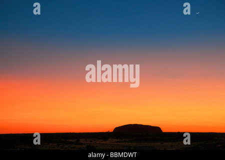 Australia, Territorio del Nord. Prima del Sunrise, Uluru o Ayres Rock si stagliano contro un magnifico rosso sangue Foto Stock