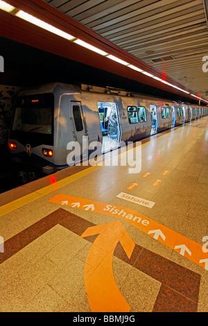 La metropolitana è in attesa con le porte aperte sulla piattaforma, una grande freccia direzionale sul pavimento, Foto Stock
