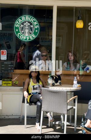 La gente seduta in uno Starbucks, Cambridge, Regno Unito Foto Stock