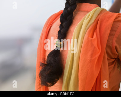 Varanasi,l'India;vista posteriore di una donna Indiana che indossa un arancione brillante sari Foto Stock
