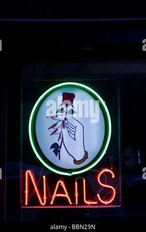 Finestra fluorescente spie visualizzate su un cinese manicurist pubblicità il loro logo chiodi in notturna a Dundee, Foto Stock