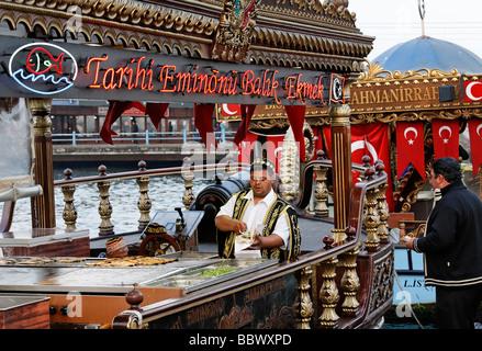 Turk in costume tradizionale preparazione del pesce i panini su una storicamente decorate in barca, Golden Horn, Foto Stock