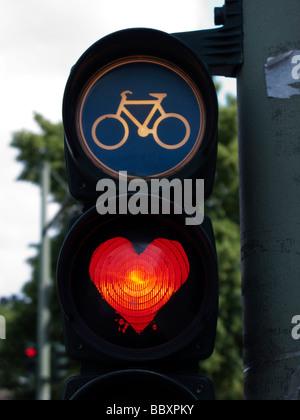 Ai semafori per i ciclisti con luce rossa dipinta a forma di cuore a Berlino Germania Foto Stock