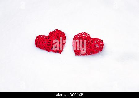 Due red Valentino cuori sul bianco della neve Foto Stock