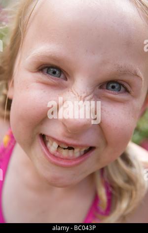 Close up di 7 anno vecchia ragazza facendo una buffa volto arrabbiato Foto Stock