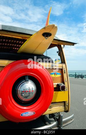 Una tavola da surf caricata su una classica vecchia auto Foto Stock