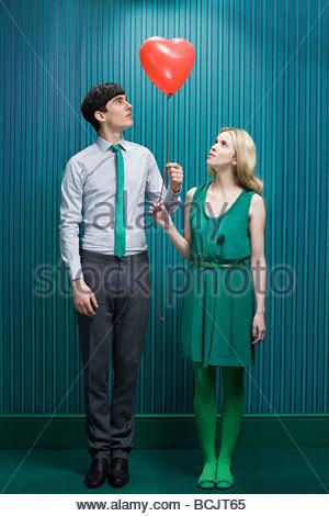Coppia con cuore palloncino di forma Foto Stock