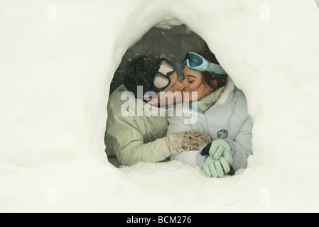 Coppia giovane baciare in igloo a occhi chiusi Foto Stock