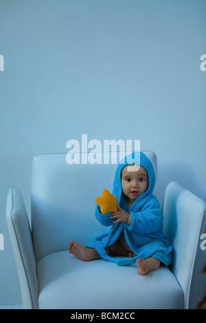 Baby boy indossare accappatoio con cappuccio seduto in poltrona, azienda giocattolo imbottito, guardando la fotocamera Foto Stock