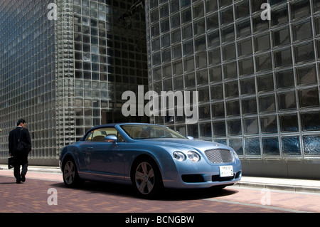 Un uomo giapponese passano da una Bentley auto di fronte della Maison Hermes edificio nel quartiere di Ginza Tokyo Giappone