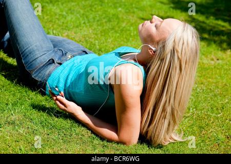 Ragazza distesa su erba ascoltando mp3 player Foto Stock