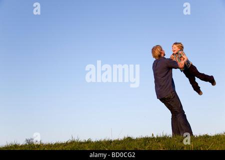 Il padre del ragazzo di filatura nelle sue braccia