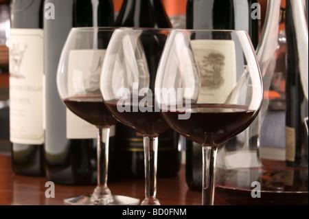 Tre vino rosso bicchieri e bottiglie Foto Stock