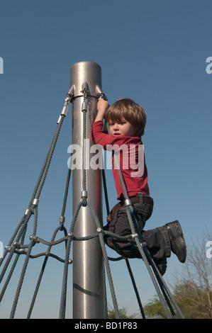 Tre anni di vecchio ragazzo nel parco giochi sulla rotazione del telaio di arrampicata Foto Stock