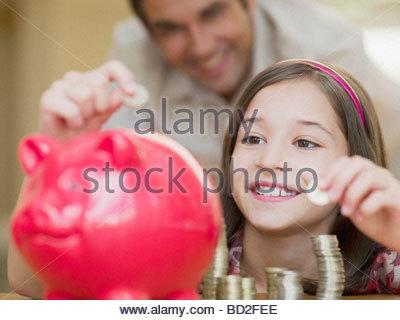 Ragazza di mettere le monete nel salvadanaio Foto Stock