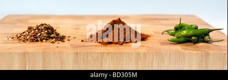 Foto panoramica di una selezione di tipi di peperoncini secchi, polverizzato e fresche, sul tagliere di legno contro Foto Stock