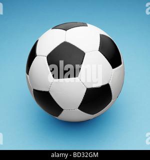 In bianco e nero in pelle / Calcio Pallone da calcio su sfondo blu. Foto Stock