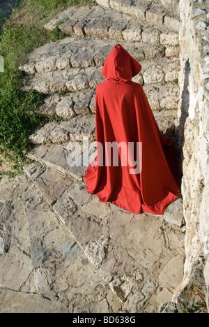 Figura misteriosa nel mantello rosso scendendo le scale di pietra Foto Stock