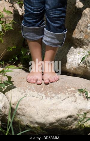Donna in piedi scalzi sulle rocce dal fiume