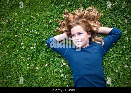Ragazza 8-12 anni giace in un campo erboso fantasticando Foto Stock