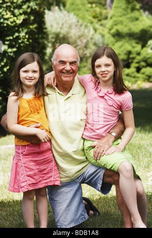 Senior uomo sorridente in un parco con la sua nipote Foto Stock