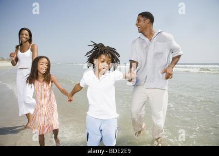Il padre e la madre giocando sulla spiaggia con la famiglia Foto Stock