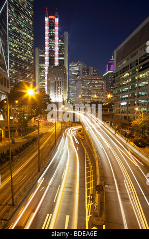 Un edificio alto e sentieri per auto a notte nel Distretto Centrale, Chung Wan, Hong Kong, Cina. Foto Stock
