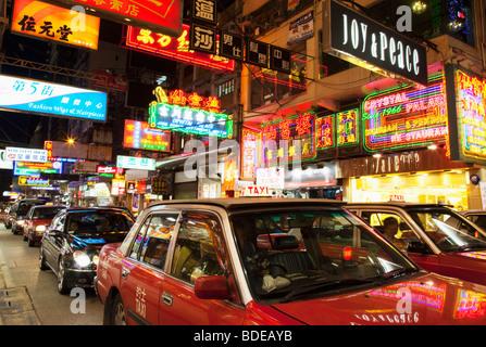 Insegne al neon e taxi nel traffico in Tsim Sha Tsui, Kowloon, Hong Kong, Cina. Foto Stock