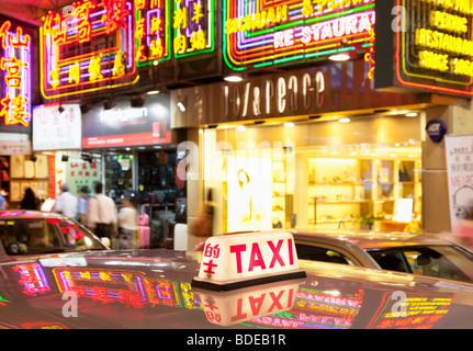Insegne al neon e taxi luce in Tsim Sha Tsui, Kowloon, Hong Kong, Cina. Foto Stock