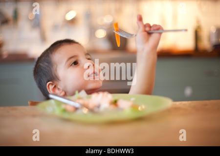 Ragazzo giocando con il suo cibo su una forcella a un tavolo da cucina Foto Stock