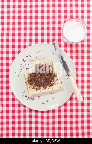 Toast cosparsi di cioccolato sulla piastra con un bicchiere di latte