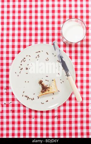Piastra con morso di pane tostato e un bicchiere di latte